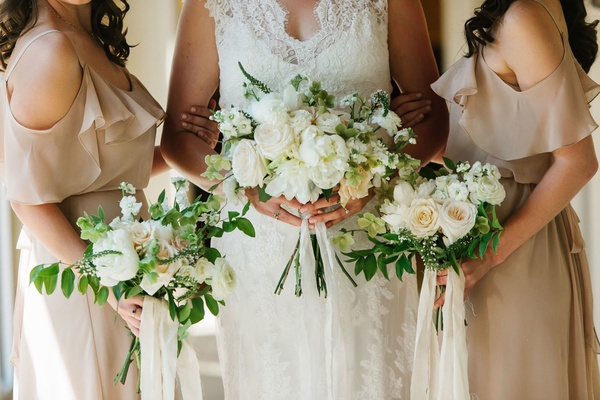 Bride with bridesmaids in tan dresses white bouquets greenery with peony rose flowers