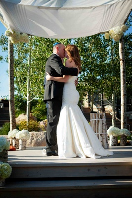 Bride and groom kiss under tallit and birch ceremony structure