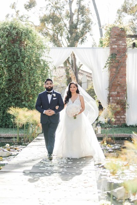 bride in hayley paige wedding dress veil big bouquet with brother on aisle with flower petals lilies