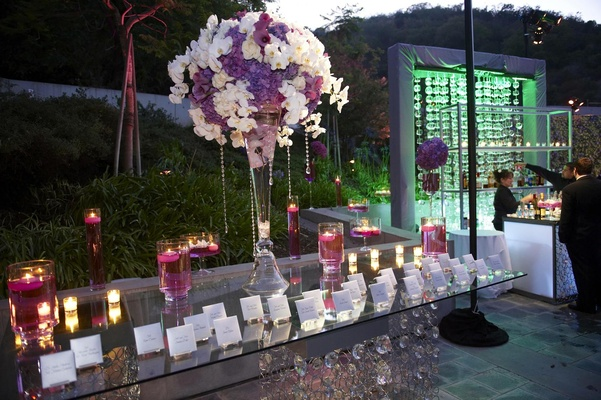 Glass table with large flower arrangement and floating candles