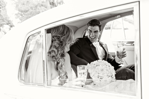 Black and white photo of bride and groom with champagne in getaway car from ceremony to reception