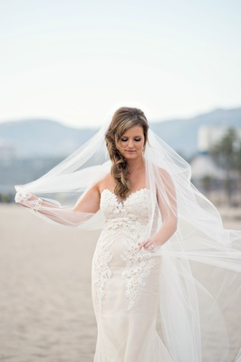 Bride in Ines Di Santo wedding dress playing with veil on beach hair to side windy day Santa Monica