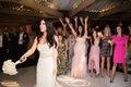 bride in vera wang does bouquet toss at wedding reception