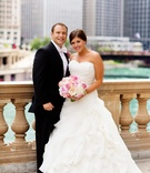 bride wearing ball gown carrying pink bouquet stands with groom in front of chicago skyline