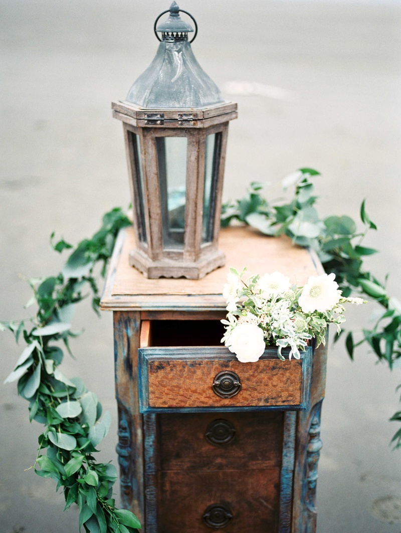 an old antique dresser with a chipped lantern white bouquet and green garland of leaves