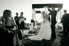 Black and white image of groom raising his bride's veil