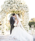 Bride in galia lahav mermaid wedding dress kissing groom in front of canopy of white flowers