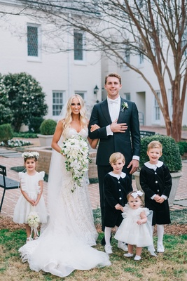 Bride and groom with cute flower girl and ring bearer in classic outfits white collars stockings