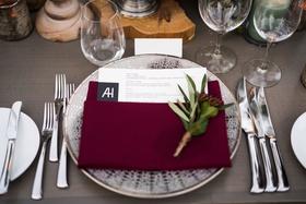 wedding reception grey wash wood table wood plank riser burgundy napkin sprig of greenery silver