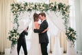 bride in j. mendel wedding dress, groom in suitsupply suit, couple hugging in front of arch