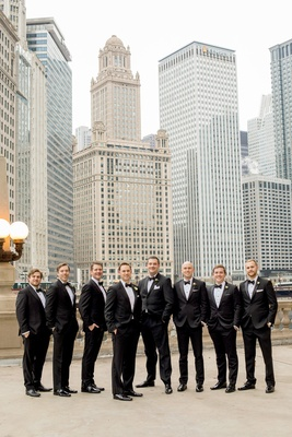 groom in hugo boss with groomsmen in black tuxedos, hands in pocket, downtown chicago