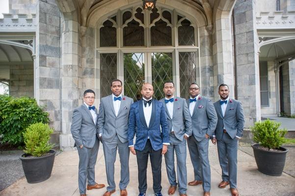 groom in navy brocade blazer from ralph lauren and black slacks, groomsmen grey suits blue bow ties