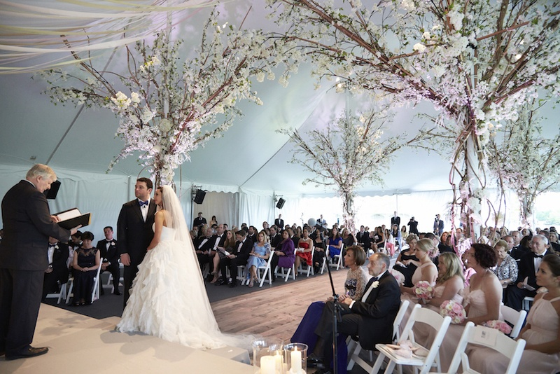 Bride and groom on stage in front of officiant with tree decorations & Ceremony Décor Photos - Rustic-Elegant Tent Wedding - Inside Weddings