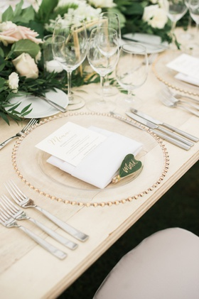 wedding reception light wood table gold clear charger menu in napkin green leaf gold calligraphy