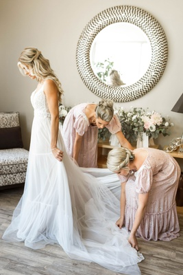 bridesmaids in vintage puff sleeve bridesmaid dresses helping bride into boho wedding dress