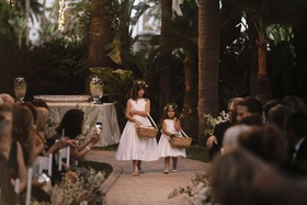 flower girls in white dresses wicker baskets with ribbon handles flower crowns stone aisle ceremony