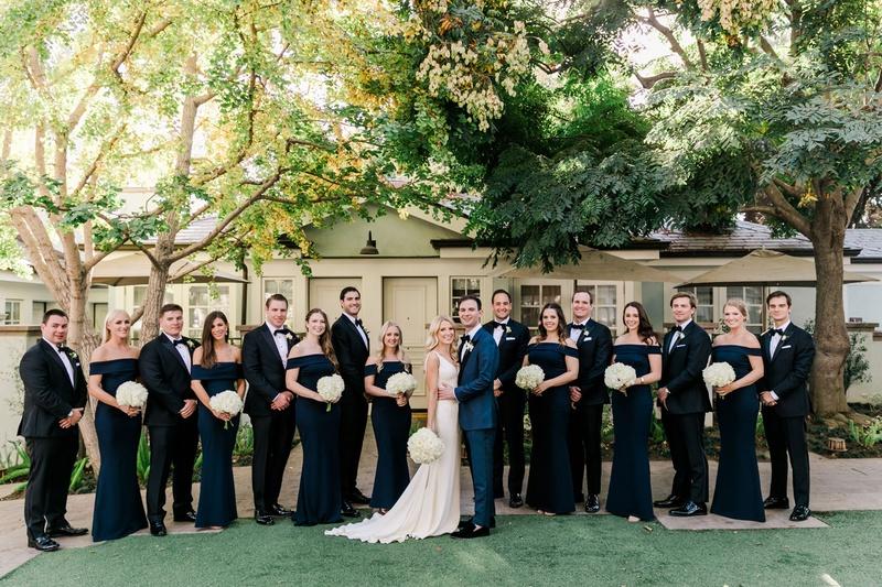 groom in blue suit with bride bridesmaids in navy blue off shoulder gowns groomsmen in suits bow tie