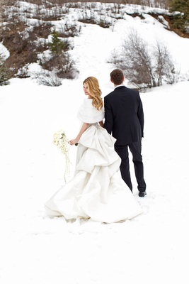 Bride in white pick-up skirt wedding dress with fur wrap shawl in snow