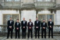 Groom in deep burgundy oxblood suit jacket and groomsmen in tuxedos and bow ties boutonnieres
