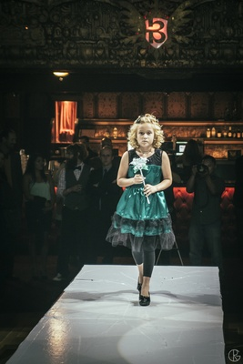 Flower girl walking down runway at theater wedding