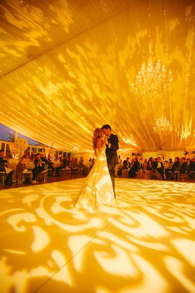 Bride and groom dancing beneath twinkling lights