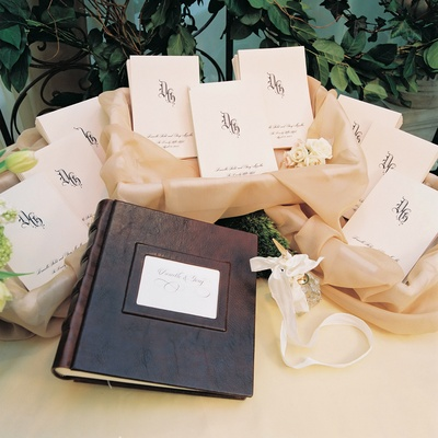 Leather-bound wedding guest book and golden pen wrapped with white ribbon