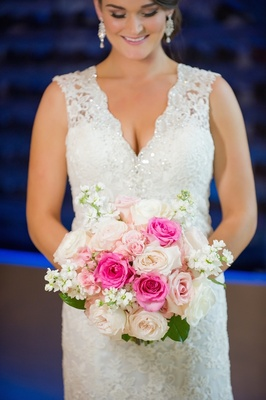 Bride wearing sparkling gown and holding pink flowers