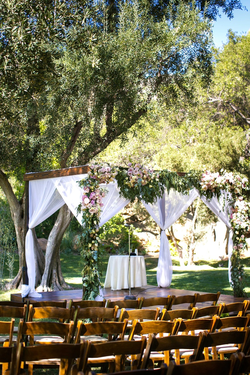 A wooden chuppah featuring foliage with light colored flowers and sheer white fabrics hanging
