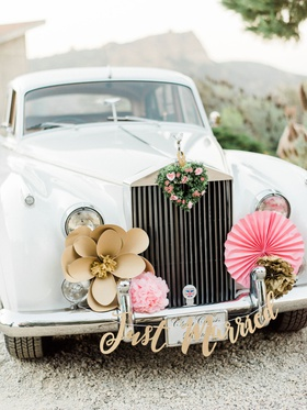 Wedding car getaway car gold flower pink fan just married sign green heart wreath