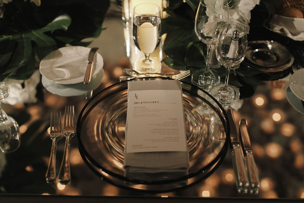 wedding reception black rim charger plate napkin menu card monogram mirror table top jungle leaves