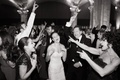 black and white photo of bride and her family dancing and singing at the reception