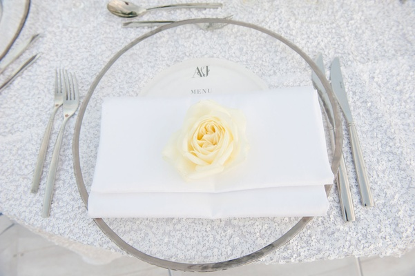 ivory rose on white napkin, clear charger with chrome rim, silver glitter linens