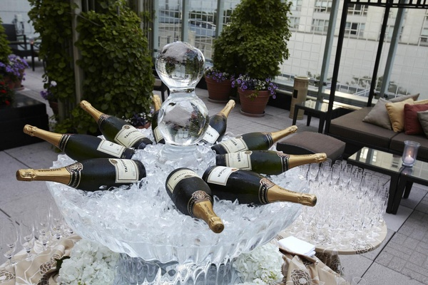 Ice sculpture carved like fountain with large champagne bottles