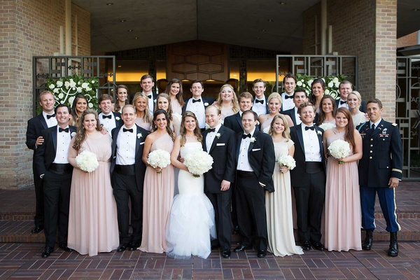 bride and groom with bridesmaids in pink dresses and groomsmen in black and white tuxedos bow ties