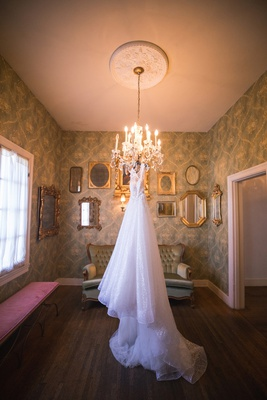 berta wedding dress with long train hanging from chandelier