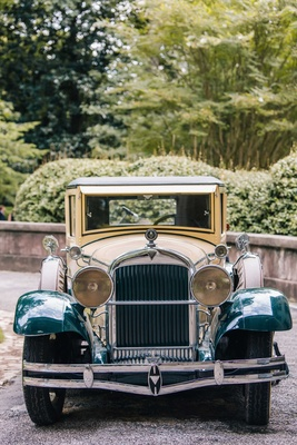 Wedding transportation classic car with green coloring to match decorations headlights 1920s