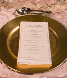 Gold wedding charger plate on satin damask linens