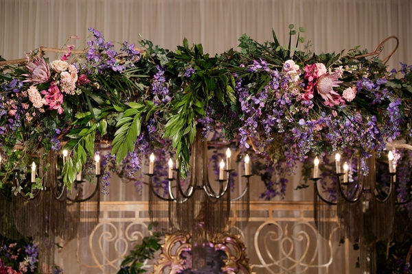 ceremony arch with purple and blush flowers, pink protea bloom, greenery, iron light fixture