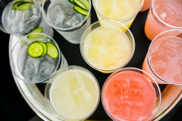 Cucumber garnish in pink and yellow drinks