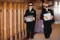 Two ring bearers in sunglasses holding safes filled with the wedding rings