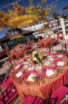orange tablecloth with pink chairs and napkins
