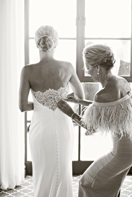 black and white photo of mother of bride helping bride put on ines di santo wedding dress