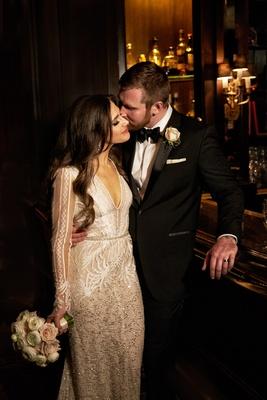 Bride in long sleeve Inbal Dror wedding dress with groom in tuxedo bow tie with long brunette hair