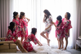 bride in white floral robe stepping into wedding gown while bridesmaids in pink robes help
