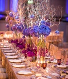 violet hydrangeas in glass column vases with branches and glass orbs. sequinned patterned linens