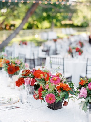 Small wedding centerpieces with pink and orange flowers with greenery