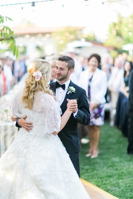 Bride in Oscar de la Renta wedding dress with cape and pink flowers in hair during first dance