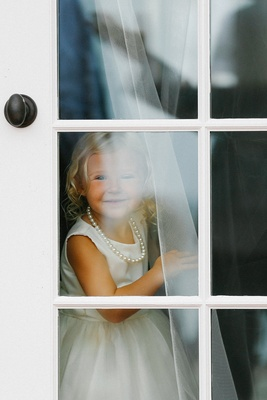 Flower girl in white dress and string of pearls looking out bridal suite window