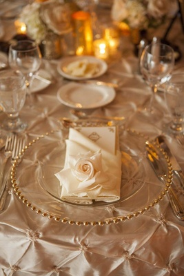 Gold-rimmed charger plate and rose