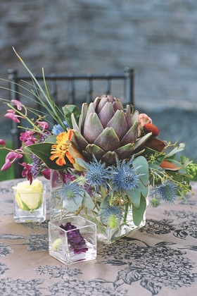 Colorful flowers and thistles in glass vase